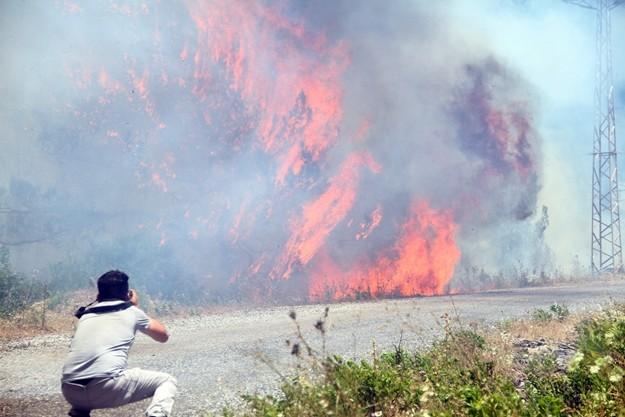 Alanya'da çıkan orman yangını rüzgarın etkisiyle büyüyerek devam ediyor. Yangın nedeniyle evler tahliye edilirken, alevlerin arasında kalan 1 arazöz ise yandı.