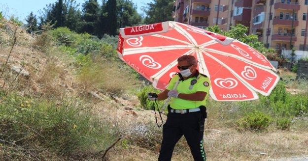 Kavurucu sıcak polis memurunu da vurdu, trafik polisi kazada plaj şemsiyesiyle görev yaptı
