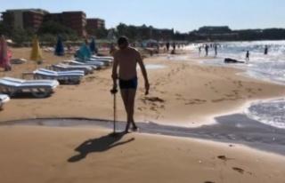 Alanya'da Rus turist elinde dedektörle sahile...